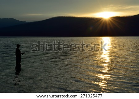 fisherman fishing in McDonald lake in Glacier National Park, Montana at sunset in summer - stock photo