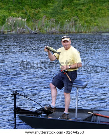 Fisherman happily displays the fish he caught.  He is standing in a boat over the water. - stock photo