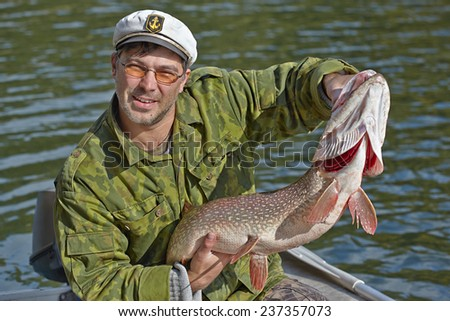 Fisherman holding a big pike - stock photo