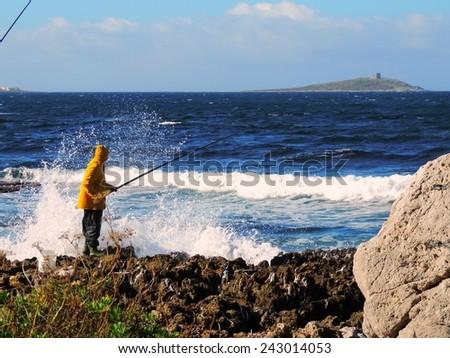 fisherman in a yellow raincoat on the seashore - stock photo