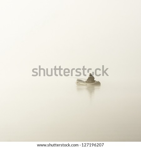 fisherman in boat in fog - stock photo