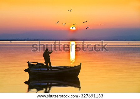 fisherman in his boat on the lake - stock photo