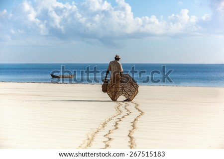 Fisherman in Kenya, water, nature, people, fishing, ocean, clouds, africa, Man fisherman early in the morning walking along the sand to the boat,  - stock photo