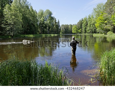 Fisherman in Swedish natural salmon area in summer - stock photo