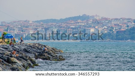 fisherman is trying to catch some fishes at the place where bosporus strait meets marmara sea. - stock photo