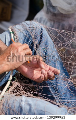 Fisherman mending his fishing nets in Cartagena, Spain - stock photo