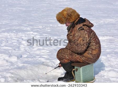 Fisherman on ice fishing on the reservoir in eastern Siberia - stock photo