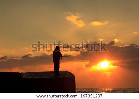 Fisherman on pier at sunset - stock photo