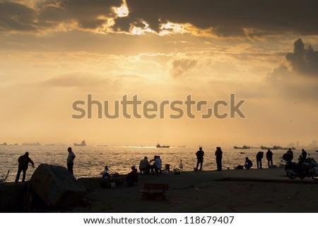 Fisherman on sunrise - stock photo