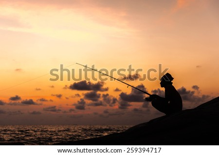 Fisherman on sunset - stock photo