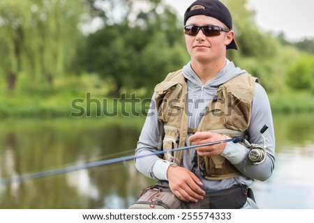 Fisherman on the river bank. Man fisherman catches a fish. Fisherman in his hand holding spinning. Fishing, spinning reel, fish, Breg rivers. - The concept of a rural getaway. Article about fishing. - stock photo