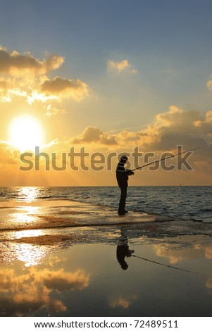 Fisherman on the sea pier at dawn - stock photo