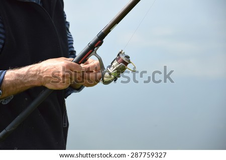 fisherman prepares bait for fish - stock photo
