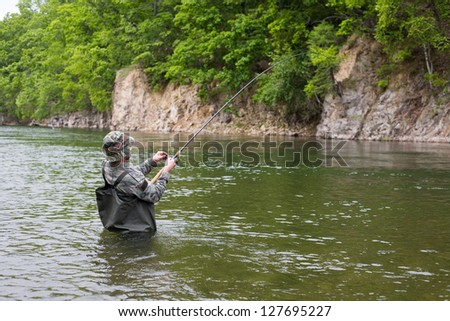 Fisherman pulls caught salmon from the river. - stock photo