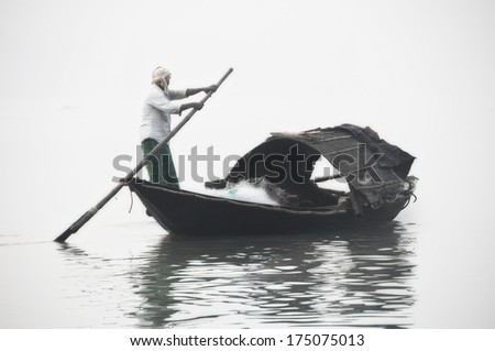 Fisherman rowing on a boat in a misty morning - stock photo