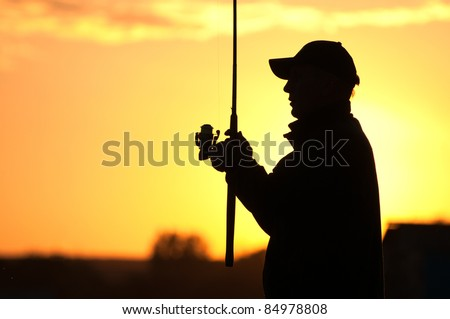 Fisherman silhouette at sunset - stock photo