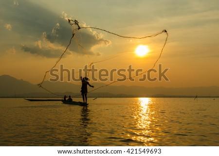 Fisherman , Silhouette fisherman with net at the lake in Thailand (kwan phayao) Phayao. - stock photo