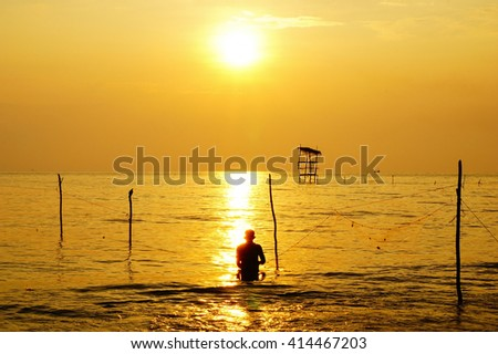 Fisherman silhouette in golden water sea reflection sunlight colorful sunrise:select focus with shallow depth of field. - stock photo
