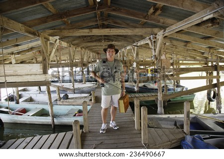 Fisherman Standing on Covered Dock at Lake - stock photo