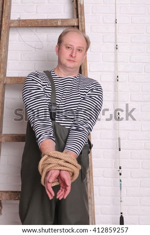 Fisherman stands near the ladder and hands tied rope - stock photo