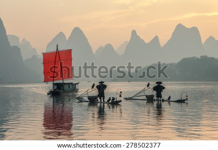 Fisherman stands on traditional bamboo boats at sunrise (boat with a red sail in the background) - The Li River, Xingping, China - stock photo