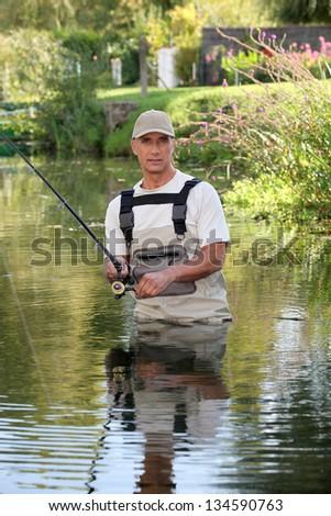 Fisherman stuck in river - stock photo