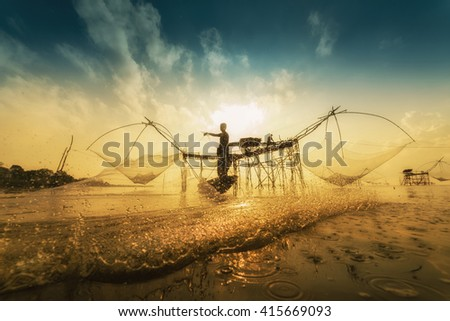 Fisherman throwing fishing net during sunrise in Pak Pra, Phatthalung, Thailand - stock photo