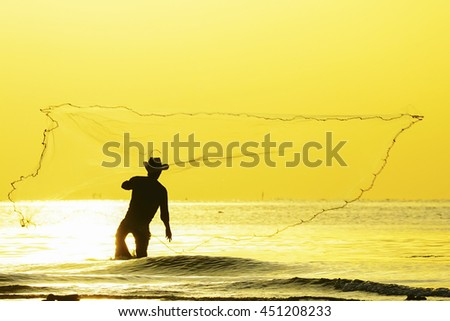 Fisherman throwing net at sunrise,select focus with shallow depth of field. - stock photo