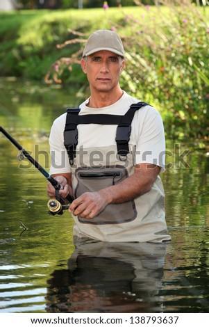Fisherman wading in river - stock photo