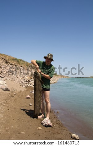 fisherman with a big catfish - stock photo