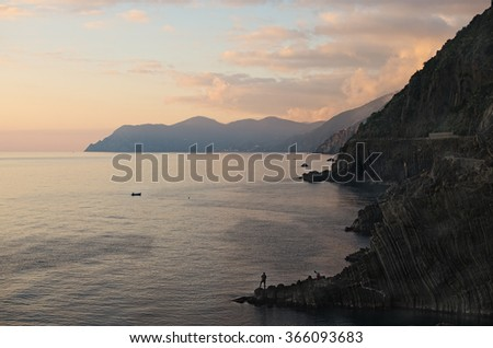 Fisherman with a fishing rod on the edge of the rock. Riomaggiore. Cinque Terre. Italy - stock photo