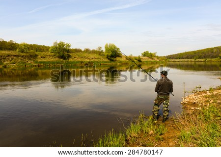 fisherman with a fishing rod on the river - stock photo