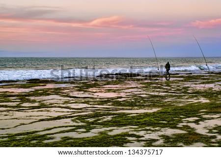 Fisherman with fishing rod on the beach, western sahara coast - stock photo