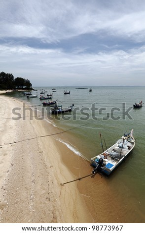 Fisherman wooden boat anchored to a rural golden beach in Penang, Malaysia, against a dramatic blue cloudy sky. - stock photo