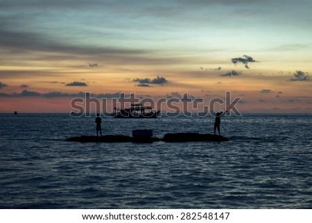 Fishermen catch fish during a beautiful sunset. Phu Quoc island. Vietnam. - stock photo