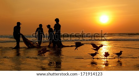 Fishermen dragged ashore network. Sunset, the Arabian Sea. - stock photo