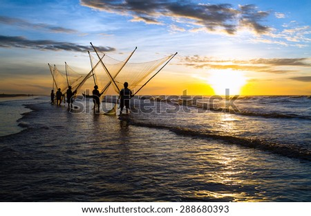 Fishermen fishing in the sea at sunrise in Namdinh, Vietnam.They wake up at 4:30 am and go out to sea to wait until the sun rises. They use a small net to scoop the seafood near the beach. - stock photo