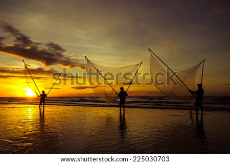 Fishermen fishing in the sea at sunrise in Namdinh, Vietnam.They wake up at 4am and go out to sea to wait until the sun rises. They use a small net to scoop the seafood near the beach. - stock photo