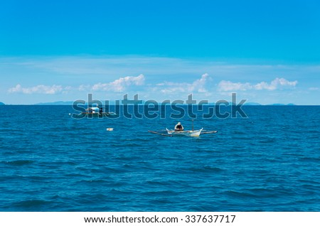 fishermen in small boats in the philippines - stock photo