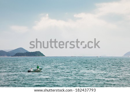Fishermen on small boat in the sea - stock photo