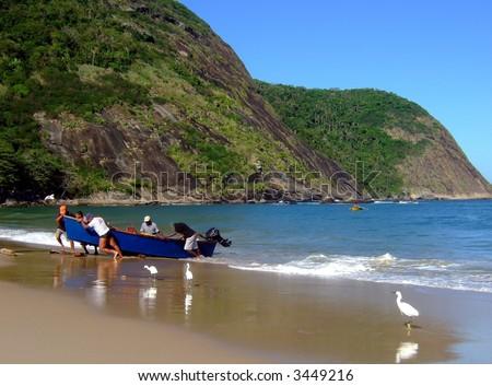 Fishermen pushing the boat in Itaipu Beach sand, Rio de Janeiro, Brazil - stock photo