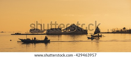 Fishermen Return to Harbour During Sunrise - stock photo