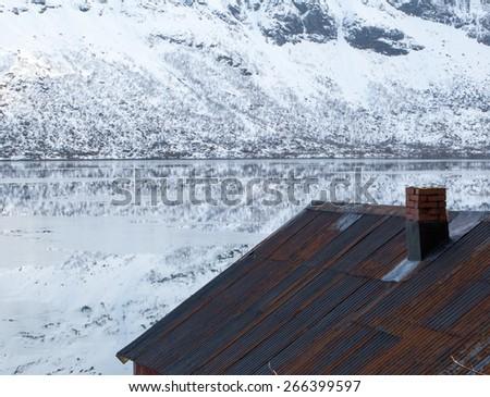 Fishermen's cabin and Winter landscape reflections, Selfjord, Lofoten, Norway - stock photo