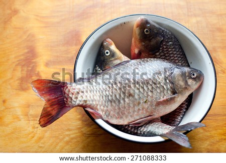 Fishes in the dish or bowl on the table in the kitchen - stock photo