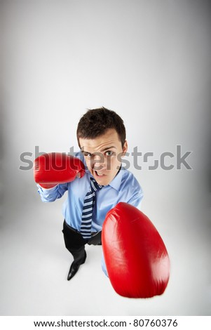 Fisheye of aggressive boxer in red gloves looking at camera - stock photo