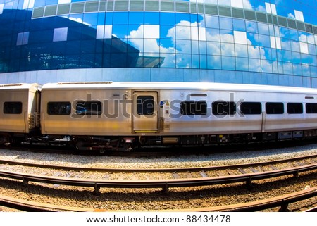 Fisheye view of a metropolitan commuter rail train with the sky reflected in the windows of a building behind - stock photo