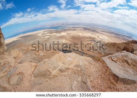 Fisheye view of desert landscape under Masada fortress near the Dead Sea - stock photo