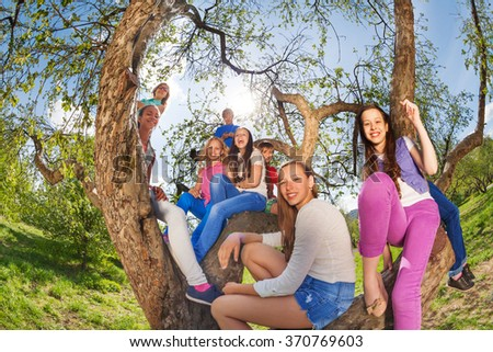 Fisheye view of smiling teenagers sitting on  tree - stock photo