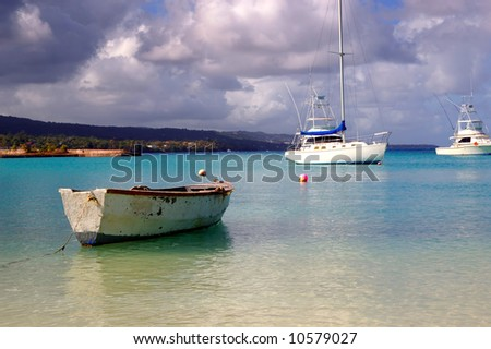 fishing boat and yachts docked at a tropical harbor - stock photo