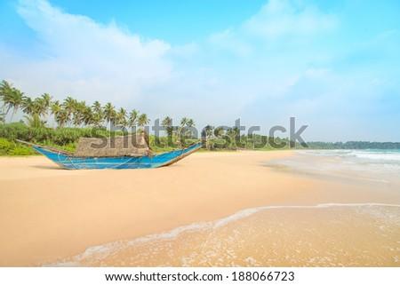 Fishing boat at beautiful sandy ocean palm beach, Indian Ocean - stock photo